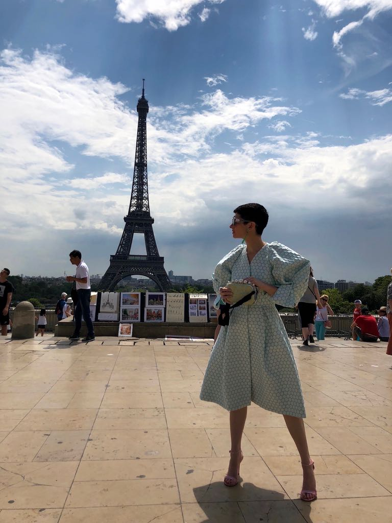 Lauren Kulchinsky Levinson poses in front of the Eiffel Tower wearing a Delpozo dress and Wendy Yue earrings. Photo courtesy