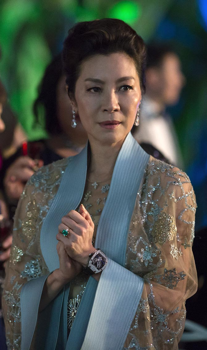 Michelle Yeoh wearing her own emerald and diamond engagement ring with diamond earrings and a Richard Mille watch in 'Crazy Rich Asians.' Photo Warner Bros.