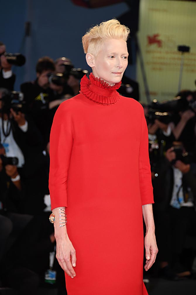 Tilda Swinton at the 'Suspiria' screening in a red gown and a custom made Delfina Delettrez gold and diamond cuff. Photo Getty