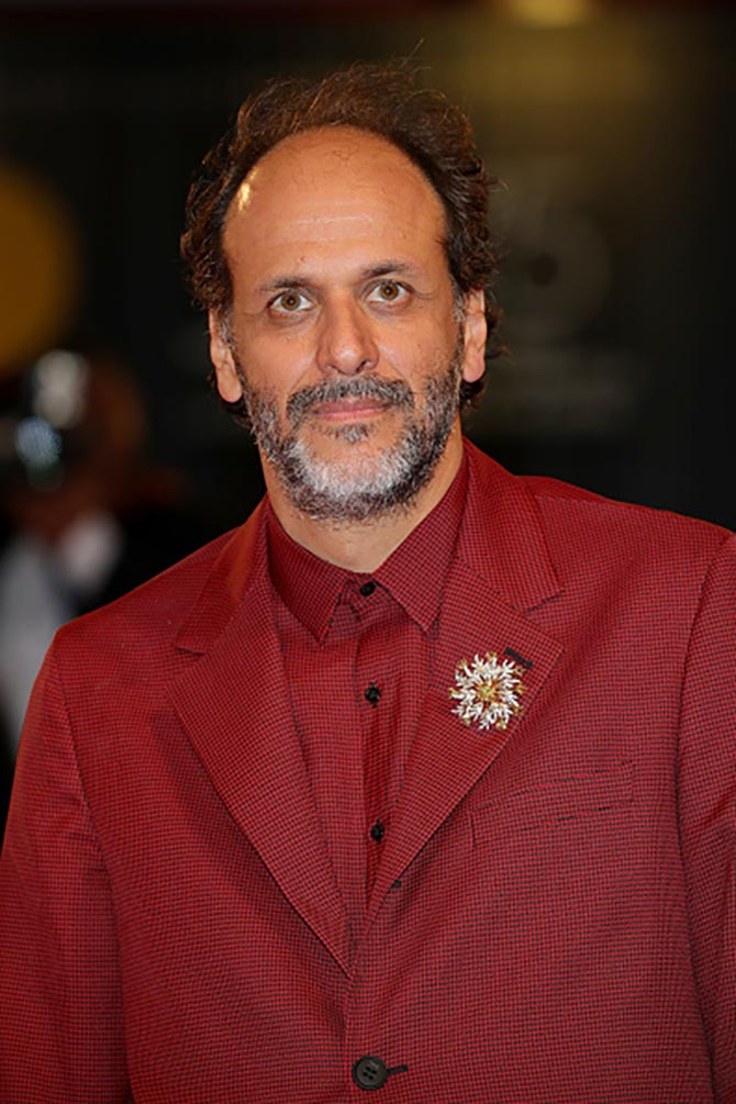 Director Luca Guadagnino at 'Suspiria' screening wore a diamond and gold brooch with a red suit. Photo Getty