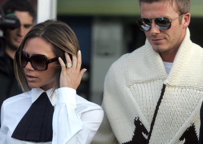 David and Victoria Beckham. She is wearing her yellow diamond engagement ring at the Rome airport in 2006.
