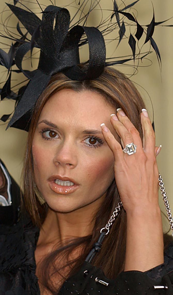 Victoria Beckham wearing her emerald-cut diamond engagement ring in 2003 for the ceremony when David Beckham was awarded the Order of the British Empire form the Queen at Buckingham Palace. Photo Getty