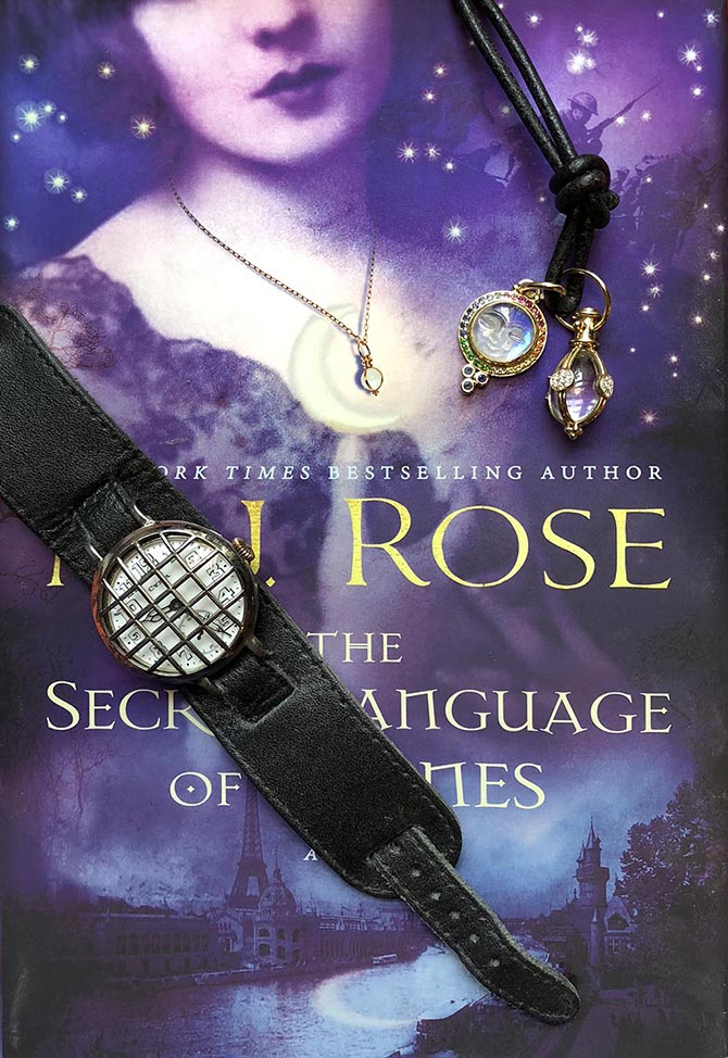 M.J. Rose's vintage trench watch and a Temple St. Clair amulet and moonface pendant on top of a copy of her book The Secret Language of Stones. Photo by Sally Davies