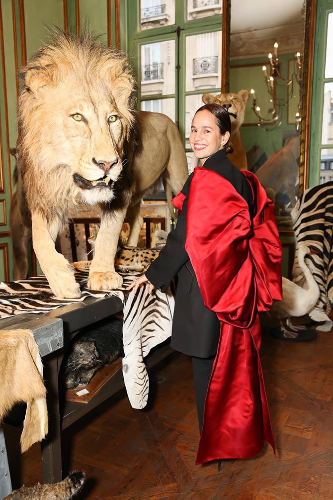 Jewelry designer Daniela Villegas wearing an Alexander McQueen ensemble poses in front of the vintage big cats at Deyrolle that died long ago of natural causes. Photo BFA