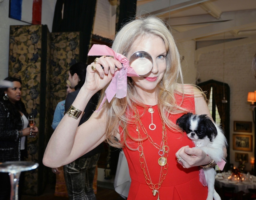 Jewelry designer Laura Lobdell holding a magnifying glass and her dog Foo at her 10th anniversary party. She is wearing a Bubble Wand necklace among many other of her designs. Photo courtesy