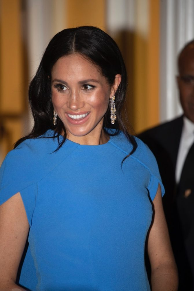 Meghan, Duchess of Sussex wearing diamond pendant earrings and a Safiyaa Ginkgo Blue Dress. Photo Getty