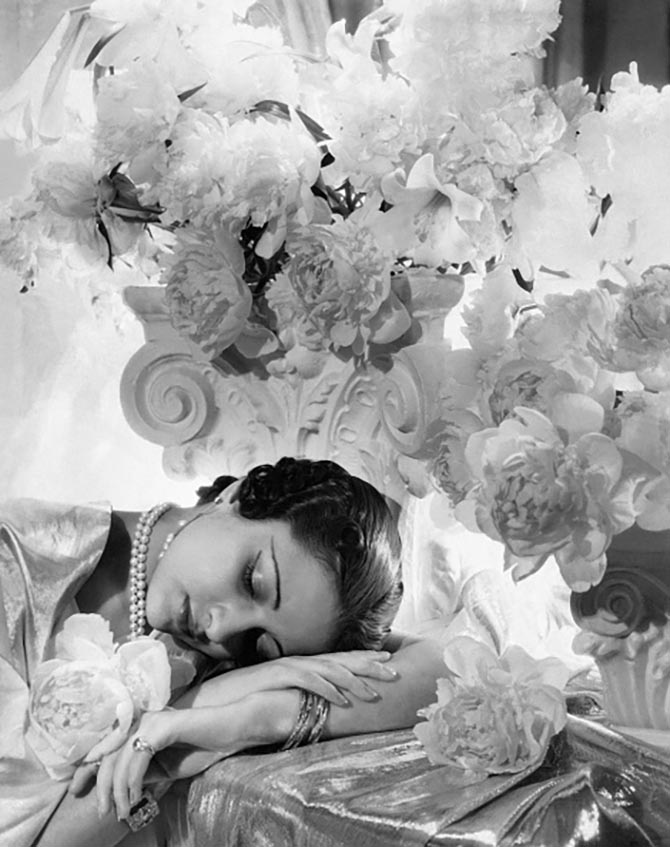 Princess Karam of Kapurthala with her head resting on her arms, surrounded by flowers and silver lame. (Photo byCecil Beaton/Condé Nast via Getty Images)