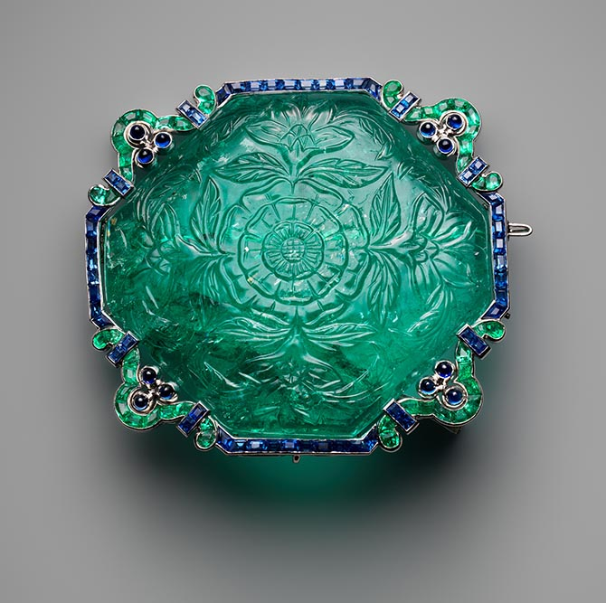 Seventeenth century carved emerald set in an emerald, sapphire and platinum Art Deco brooch by Cartier. Photo courtesy of the Metropolitan Museum of Art