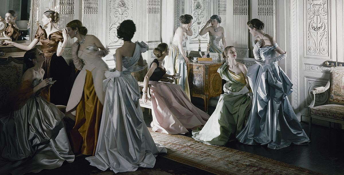 Nine models (including Marilyn Ambrose, Dorry Adkins, Carmen Dell'Orefice, Andrea Johnson, Lily Carlson, and Dorian Leigh) wearing Charles James gowns, in French & Company's eighteenth century French paneled room
