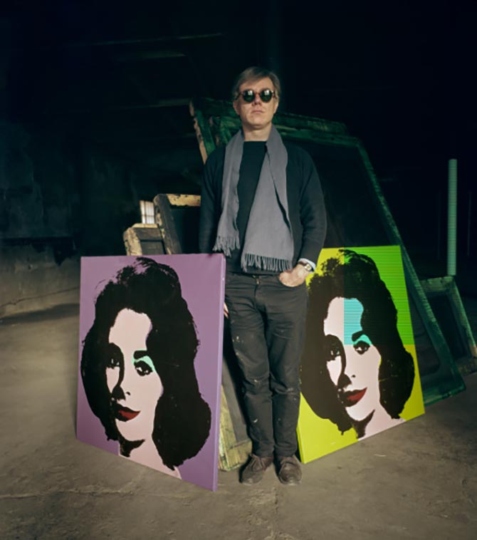 Andy Warhol posing with two his prints of Elizabeth Taylor in New York around 1964. Photo Evelyn Hofer/Getty Images
