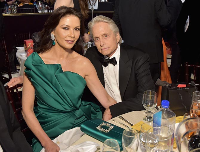 Michael Douglas with Catherine Zeta-Jones in Lorraine Schwartz emerald and diamond earrings.