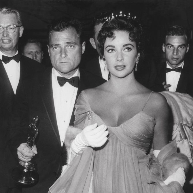 Mike Todd holding his Oscar while he walks with Elizabeth Taylor who is wearing her antique tiara. Photo Rex