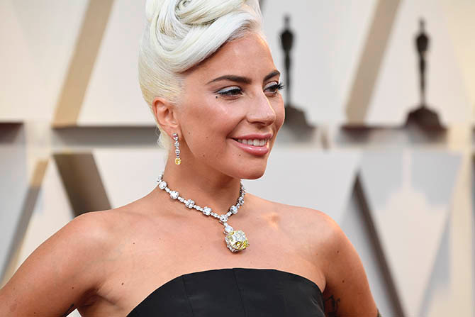 Lady Gaga wearing the 128.54-carat Tiffany diamond in a diamond necklace with coordinating earrings.