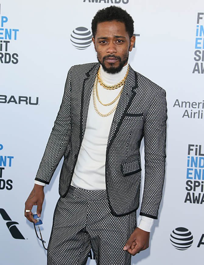 Lakeith Stanfield wore three gold necklaces with his turtleneck and suit.