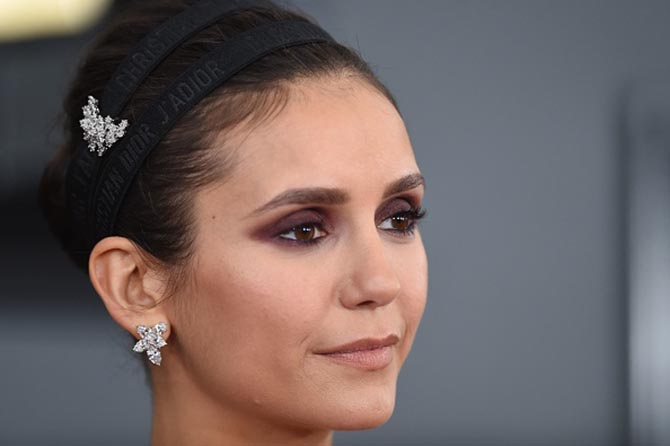 Nina Dobrev wore Harry Winston diamond cluster earrings and a diamond crescent brooch at the Grammys