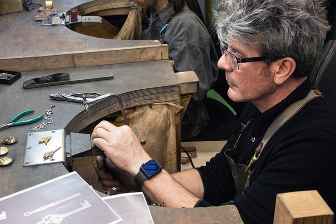 Jeweler Stephen Einhorn working on the the key pendant worn by Nico Parker in 'Dumbo.' Danny Devito's pocket watch is on top of the jeweler's bench. Photo courtesy