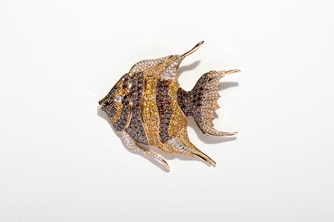 The Chopard Animal World fish brooch worn by Taraon Egerton is composed of in 18-karat yellow gold set with brown diamonds, yellow sapphires and diamond brilliants.