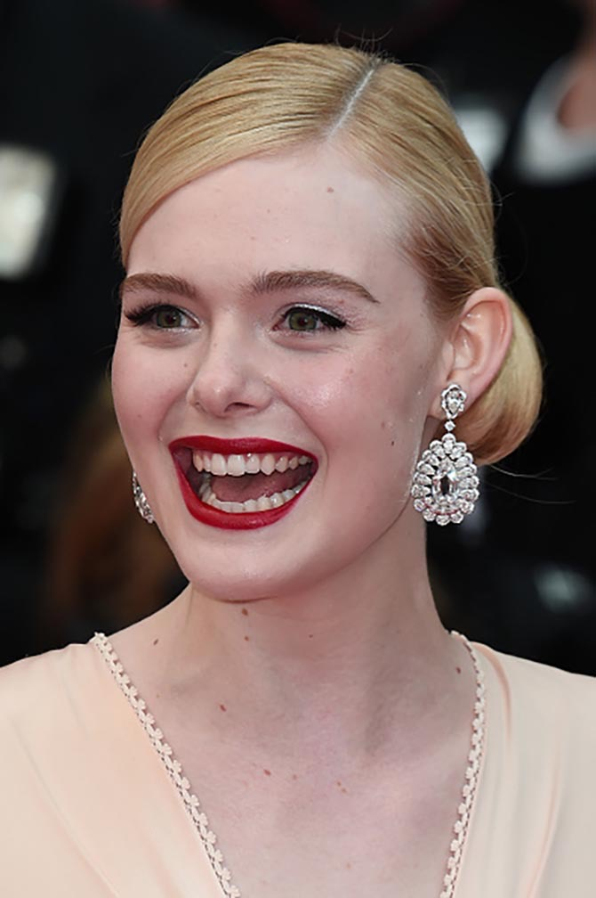 Elle Fanning wearing Chopard earrings poses as she arrives for the screening of the film 'The Dead Don't Die' during the 72nd edition of the Cannes Film Festival in Cannes on May 14, 2019.