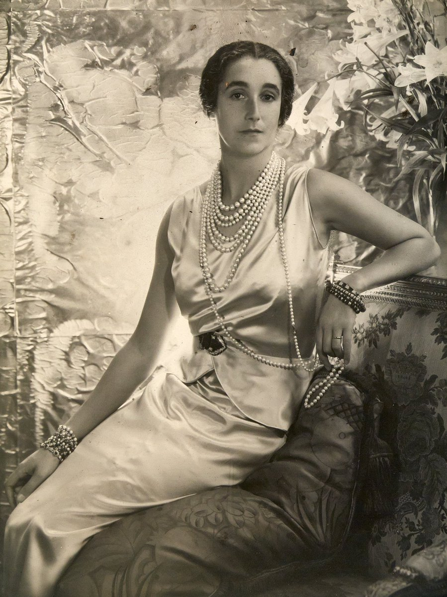Sybil Sassoon, Marchioness of Cholmondeley wearing the Cartier Art Deco brooch at her waist with other important jewels. Photo via @HoughtonHallNorfolk