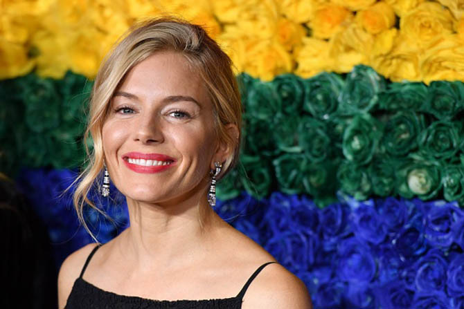 Sienna Miller wore earrings by Cartier with her black dress.