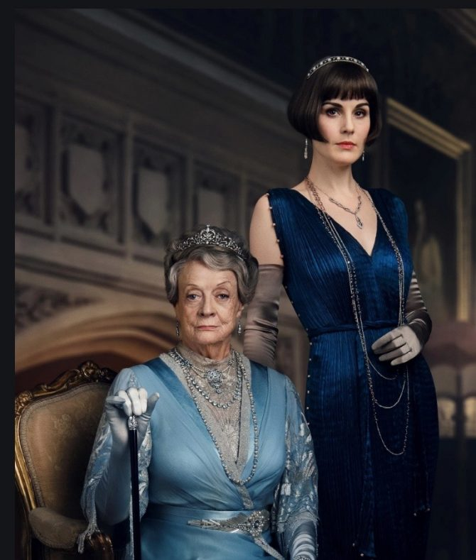 The eternally elegant Lady Mary (Michelle Dockery), now settled into her own career running Downton, is thoroughly accessorized for every occasion, with many layers of coordinating beads and bracelets, her bob crowned with a sparkling headband style bandeau for the dinner hosted by the King and Queen.