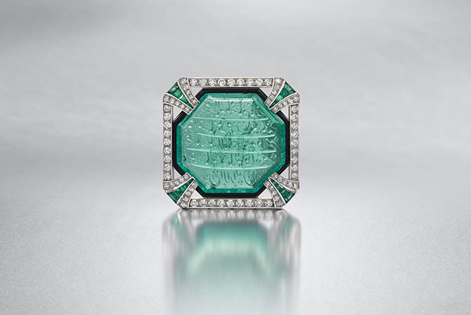 LONDON LOT 133 – An Art Deco emerald, diamond and enamel brooch by HENNELL, circa 1925, Containing an engraved emerald, dated 1813-1814, probably presented by the Mughal Emperor Akbar II (Reg. 1806-1837) to Mary Hood