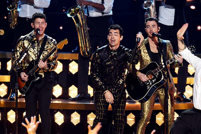 Nick Jonas, Joe Jonas, wore pearl necklaces as they performed with their brother Kevin Jonas