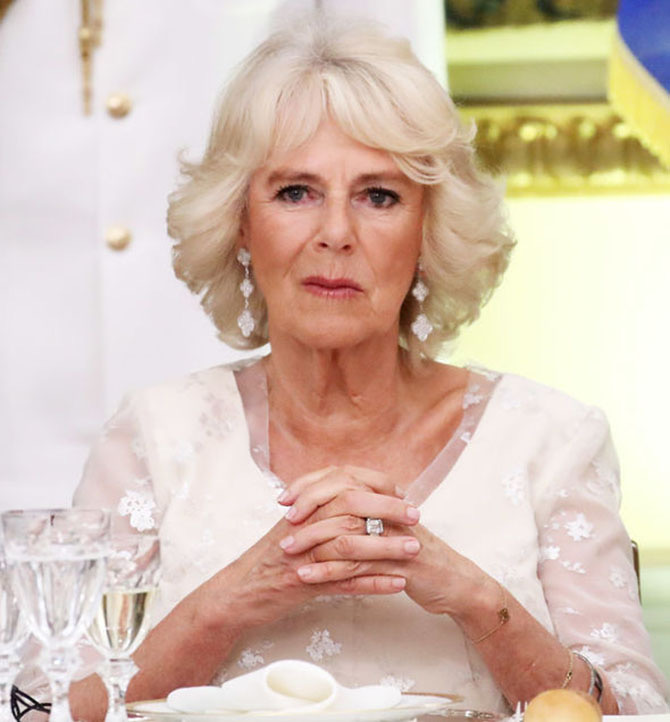 Camilla Parker Bowles wearing Van Cleef & Arpels diamond and white gold Alhambra earrings and her engagement ring. Photo
