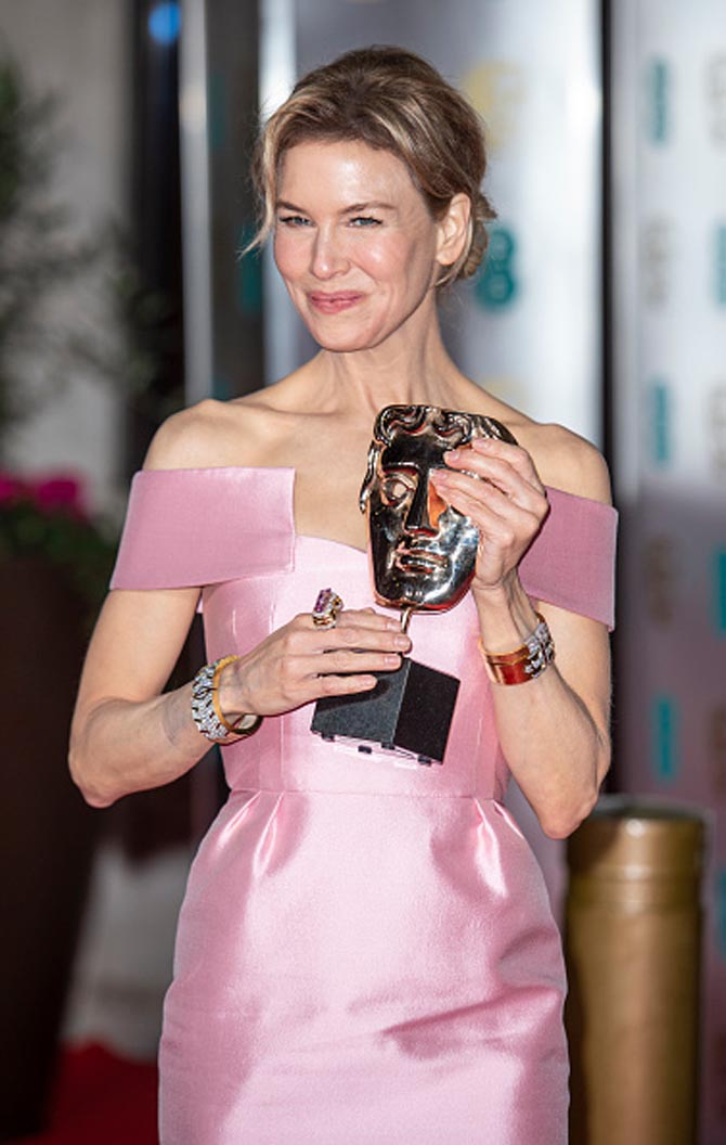 Renee Zellweger wore David Webb's diamond, gold and platinum Parentheses Bracelet, Deco Riff Cuff, Sugar Cube Bangle, and Kunzite Ring to the73rd British Academy Film Awards in London on February 2, 2020. Photo Getty