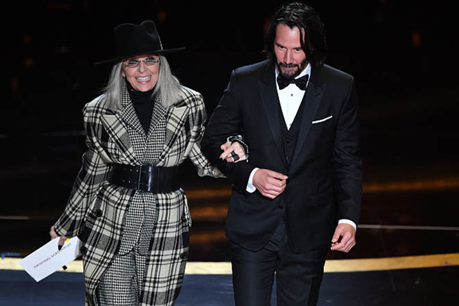Diane Keaton wearing Nancy Newberg rings walks on stage at the Oscars with Keanu Reeves who is wearing in Cartier shirt studs.