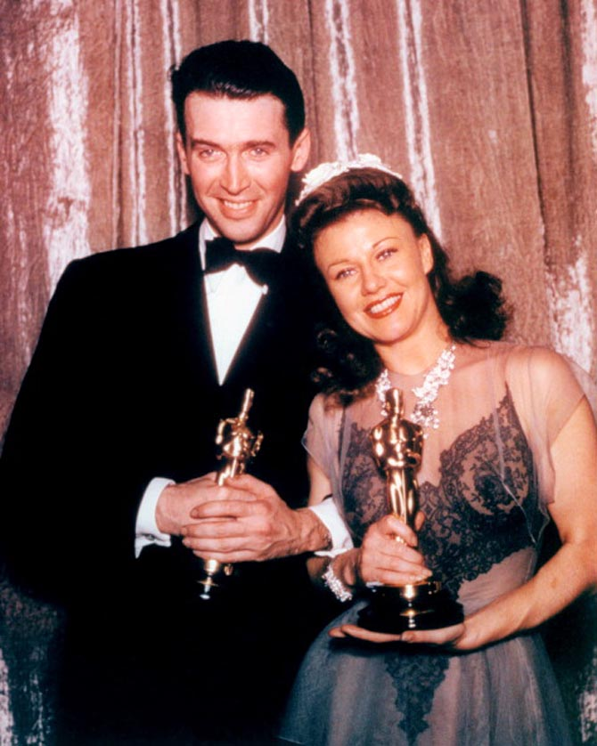 James Stewart (1908-1997), US actor, wearing a black tuxedo, a white shirt and black bow tie, with Ginger Rogers (1911-1995), US actress and dancer, wearing an evening gown, both holding their Oscar statuettes, at the 13th Academy Awards, at the Biltmore Hotel in Los Angeles, California, USA, 27 February 1941. Stewart won Best Actor in a Leading Role for his performance in 'The Philadelphia Story', and Rogers won Best Actress in a Leading Role for her performance in 'Kitty Foyle'. (Photo by Hulton Archive/Getty Images)