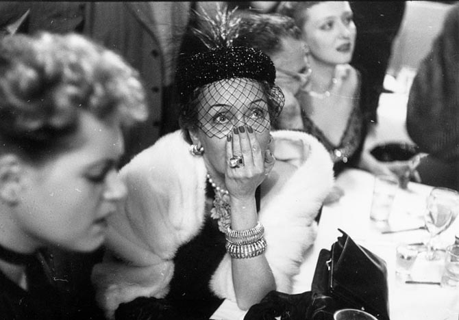 American actress Gloria Swanson (1899 - 1983, centre), anxiously awaits the results of the Best Actress award at the La Zambra nightclub at 127 W. 52nd Street, New York City, during a live radio link with the Oscars ceremony in Los Angeles, 29th March 1951. On her left is her fellow nominee and the eventual winner, Judy Holliday (1921 - 1965). (Photo by Slim Aarons/Getty Images)