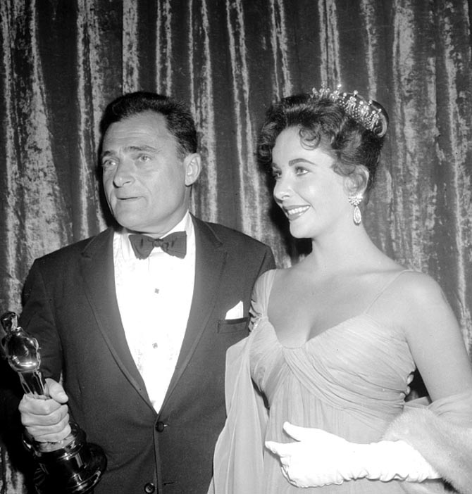 LOS ANGELES - MARCH 27: Actress Elizabeth Taylor in tiara attends the 29th Academy Awards ceremony which was held at the RKO Pantages Theatre with her second husband producer Mike Todd, who holds the Oscar he won for best picture for his film 'Around The World In 80 Days', on March 27, 1957 in Los Angeles, California. (Photo by Michael Ochs Archives/Getty Images)