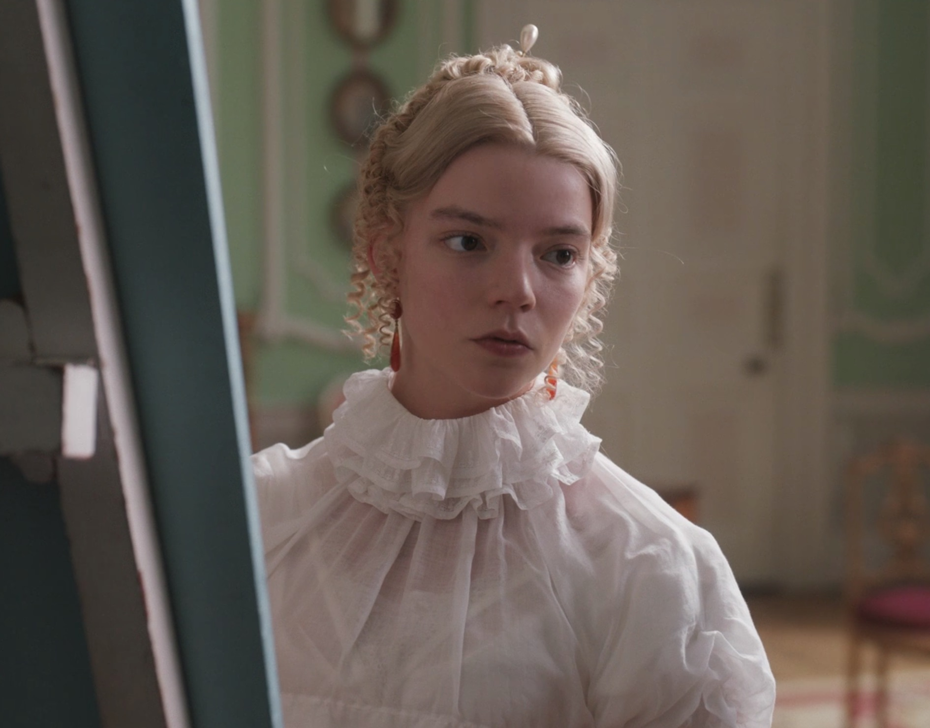 Emma (Anya Taylor-Joy) wearing pendant earrings and a pearl hair pin while she paints a portrait. Photo Focus Features